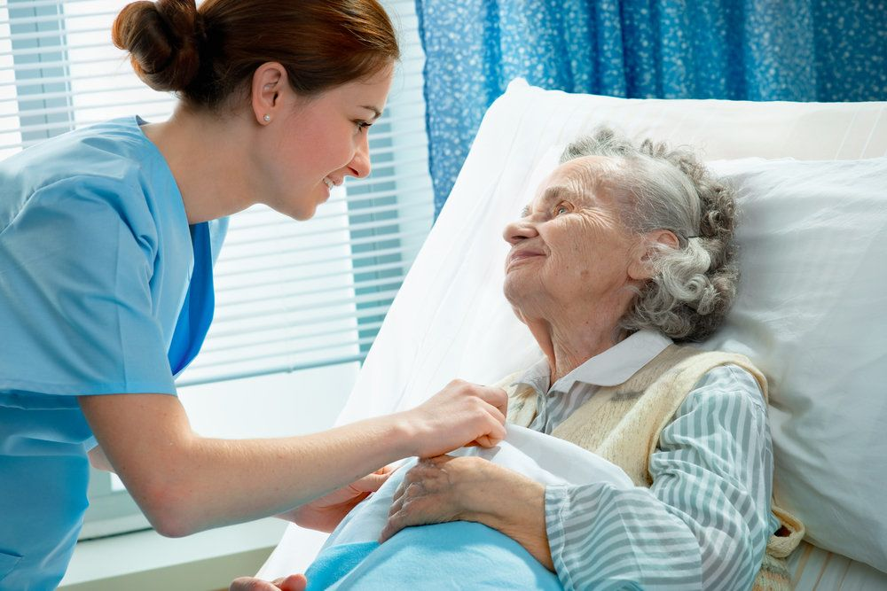 Elderly woman in hospital bed smiling at nurse