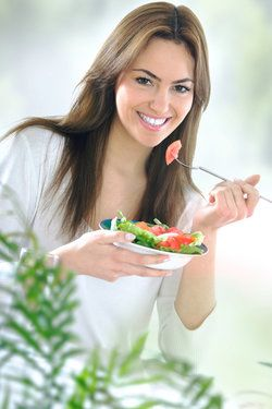 A young woman eating a salad