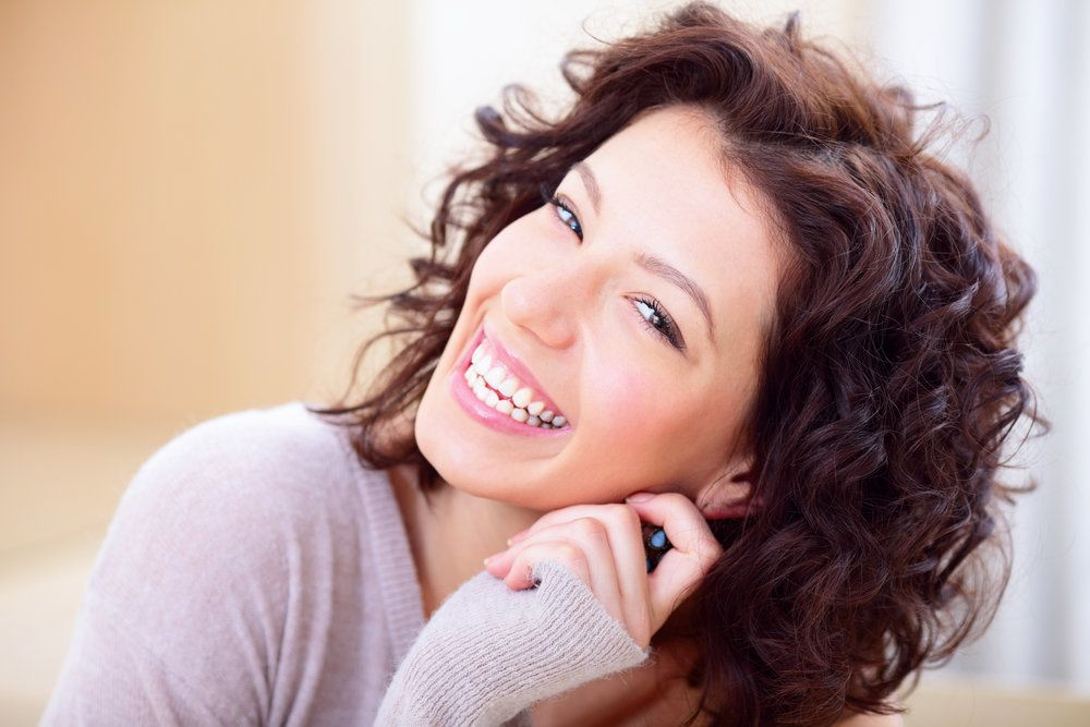 A brunette woman with fillings smiles confidently