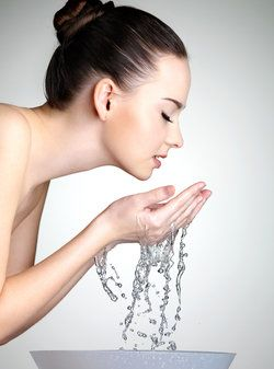 Woman with glowing, youthful skin splashing water on face