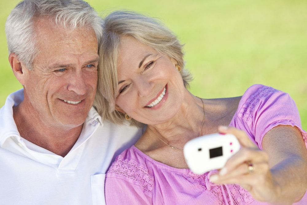An elderly couple looking at digital photos, the wife showing off her implant-supported dental bridge by smiling broadly