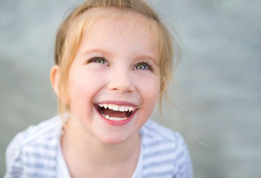 Young Caucasian girl laughing with eyes turned skyward