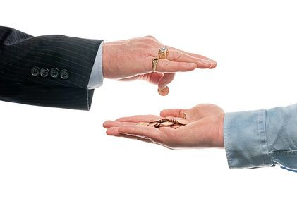 Businessman dropping coins into man's hand