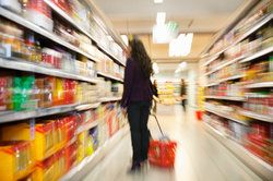 A woman standing in the aisle of a drug store, looking at shelves hopefully not stocked with defective products
