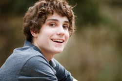 Smiling teenage boy with curly brown hair
