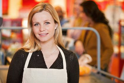 Smiling young blond woman wearing checkout clerk outfit