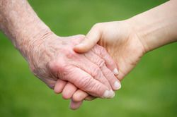 An older person holding hands with someone younger