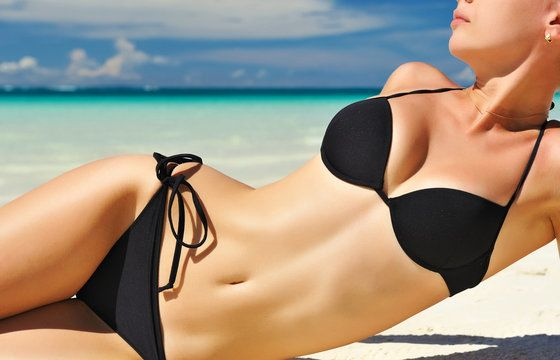 Woman in black bikini on beach after thermitight procedure