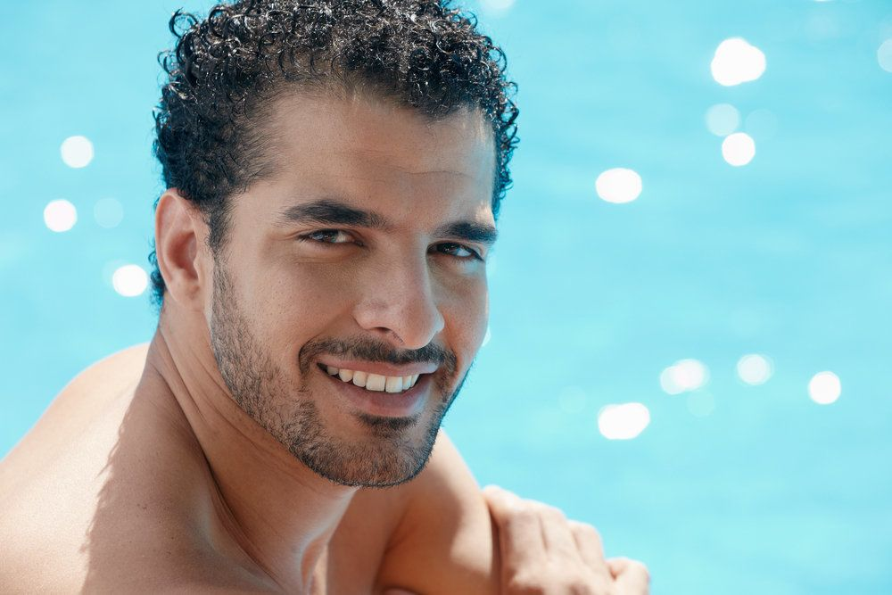 A man smiling beside a swimming pool, pleased that he can see clearly without glasses or contact lenses thanks to LASIK surgery
