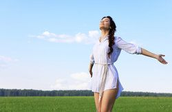 Woman in short white shirtdress in field throwing head back and arms wide