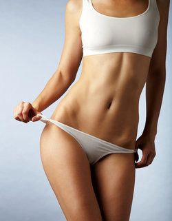 Woman with toned, sculpted midsection holding white underwear off hipbone