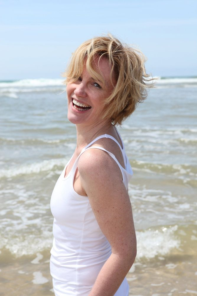 A woman at the ocean smiling at the camera