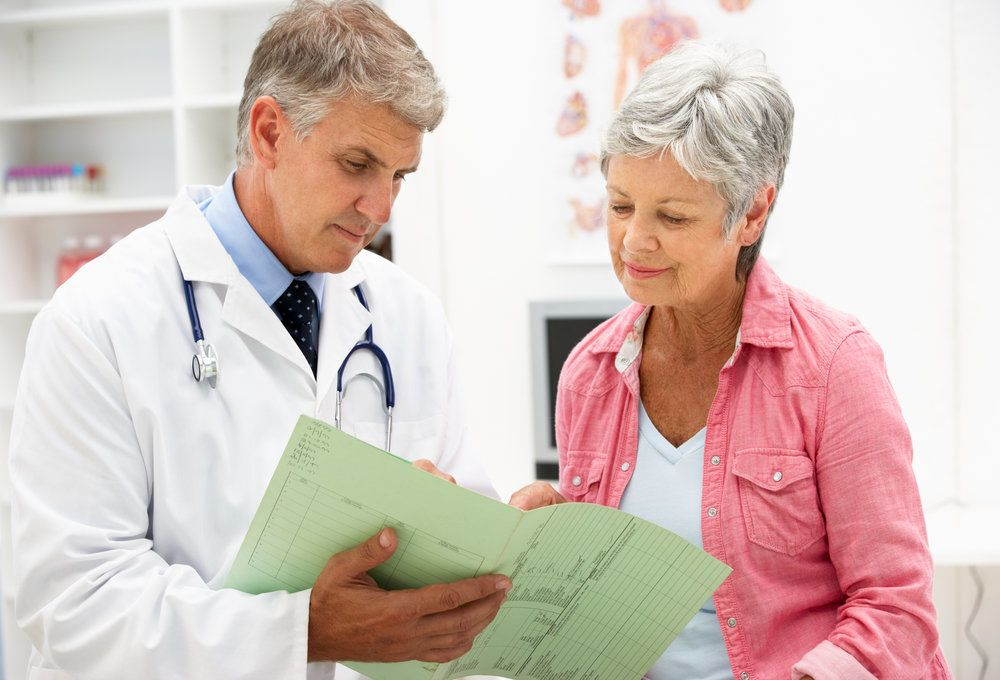 Older woman looking at medical files with doctor in doctor's office.