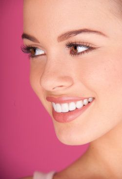 A beautiful, young woman with brown eyes smiles in front of a pink background.
