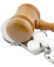 Wooden gavel resting on pills and handcuffs