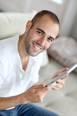 A handsome man holding a tablet.
