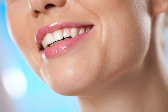 Lower portion of woman's smiling face and lips with pink gloss