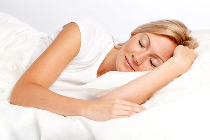 A beautiful blonde woman wearing all white sleeps in a white-linen bed.
