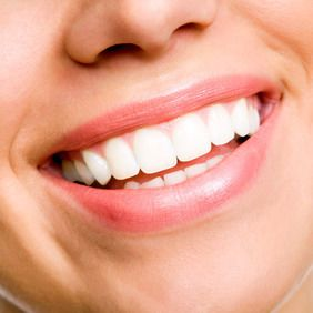 A close-up of a woman's healthy, white smile