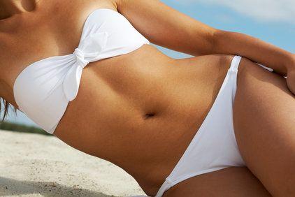 Torso of attractive woman in white bikini sunbathing on beach