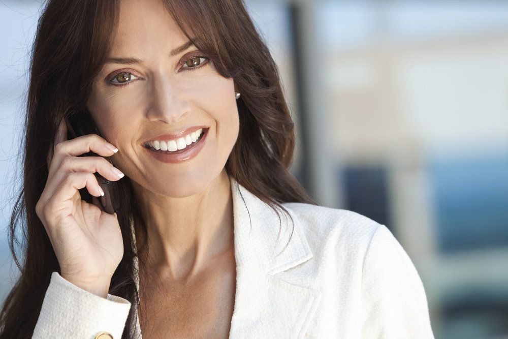 A woman smiles while on the phone