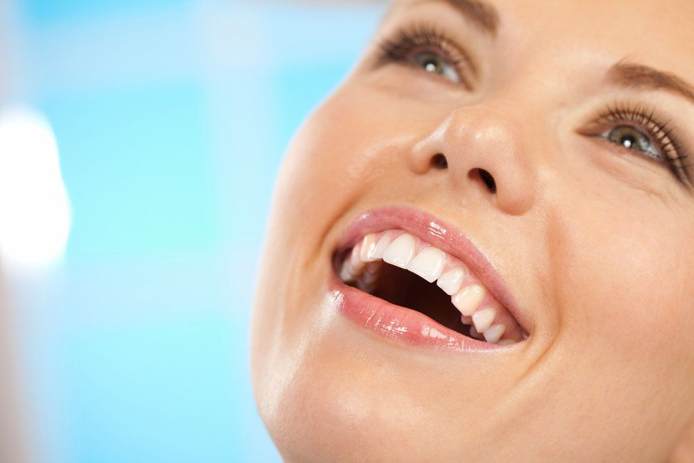 Close-up of smiling woman with healthy white teeth.