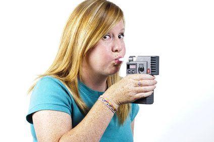Redheaded teenage girl blowing into breathalyzer machine