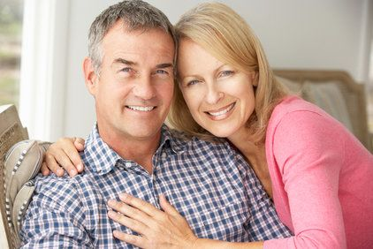 An attractive middle-aged couple sit on their porch while smiling and hugging.