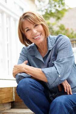A middle-aged woman wearing a denim top and pants crouching down on a deck.