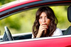 A brown-haired woman looking distraught behind the wheel