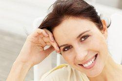 Smiling brunette resting cheek on hand