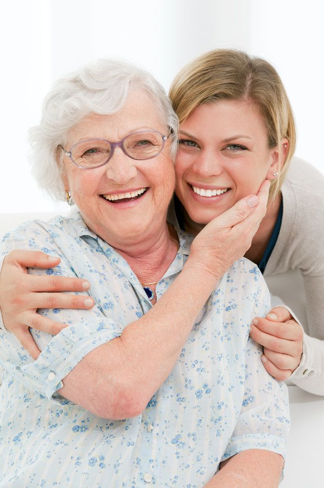An older woman and her younger relative smiling