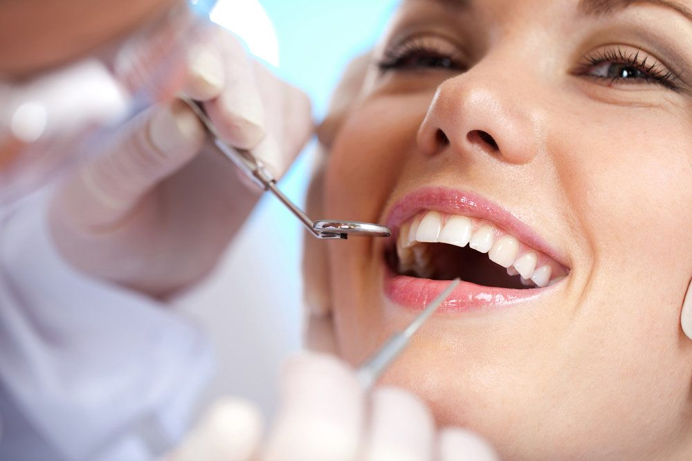 A close-up of a woman with healthy, white teeth, undergoing a dental exam