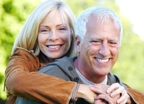 Smiling older couple with woman wrapping arms around man's shoulders