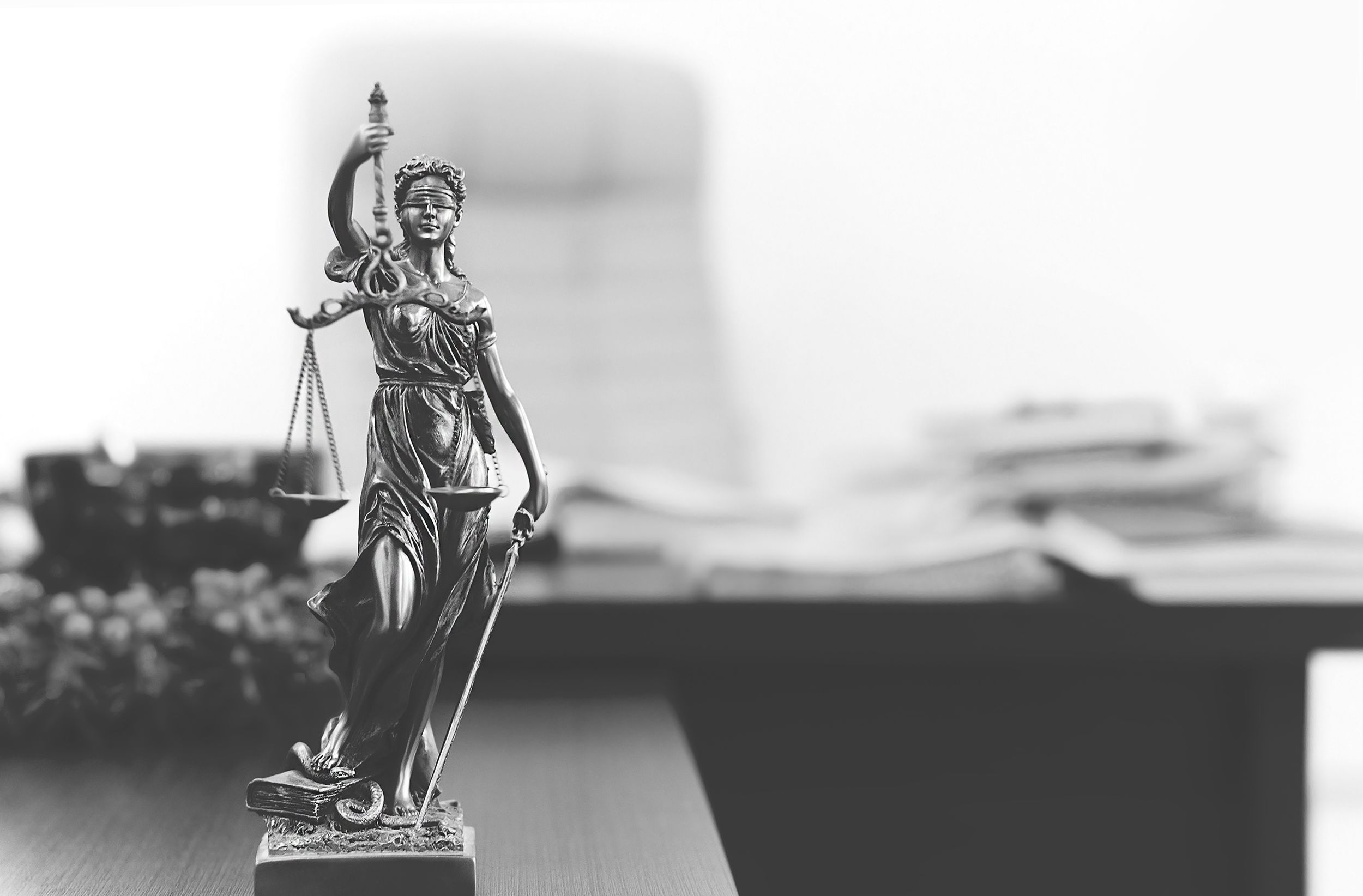 A statue of lady justice on a lawyer's desk