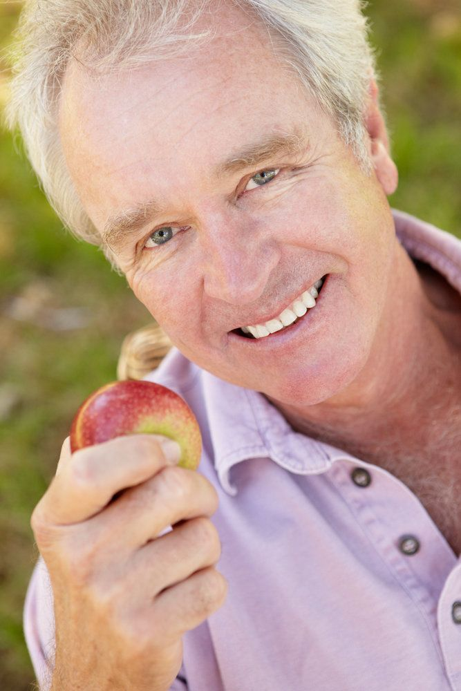 Older man holding an apple