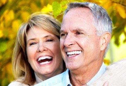 Laughing middle-aged couple with straight, white teeth