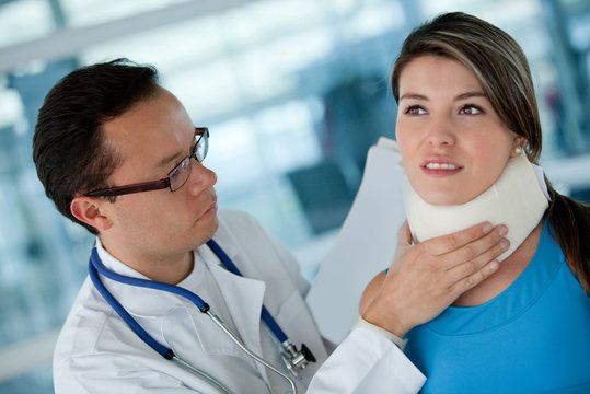 A woman in a neck brace being treated by a doctor