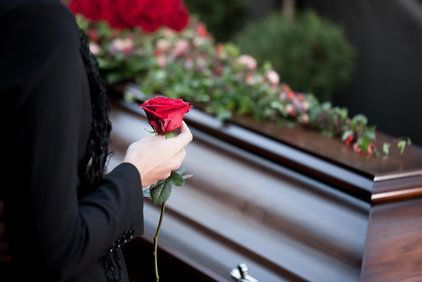Mourning woman holding rose in front of casket