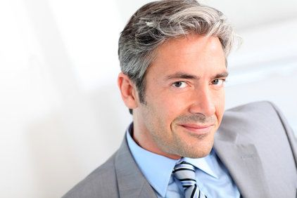 Businessman with thick gray hair smiling slyly