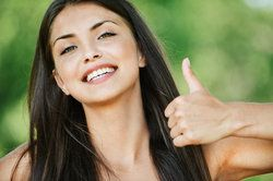 A smiling woman gives a thumbs up