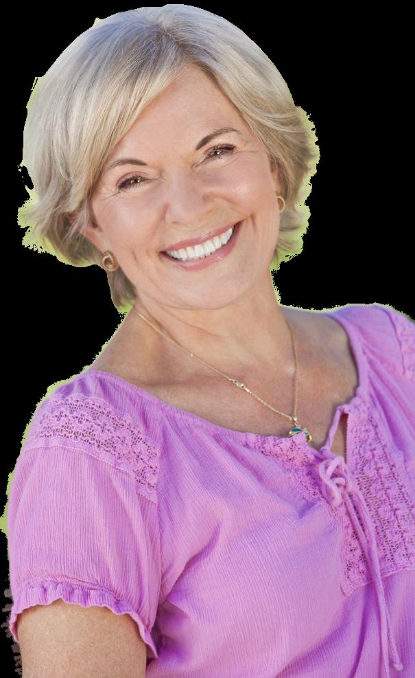 An elderly woman wearing a purple shirt smiles in the green grass.