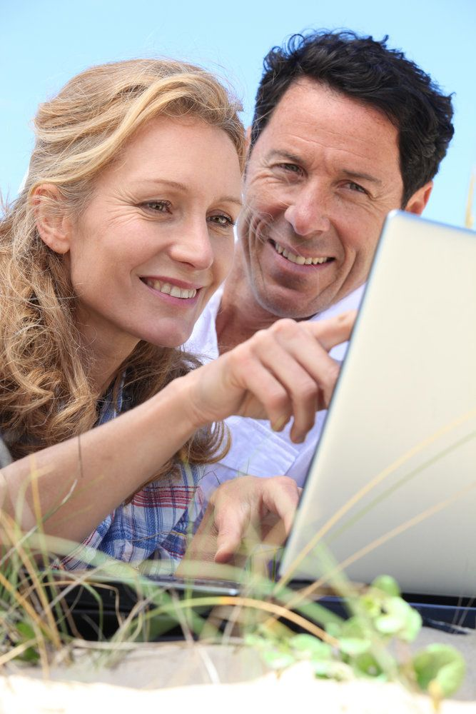 A woman and a man looking at a computer screen after LASIK