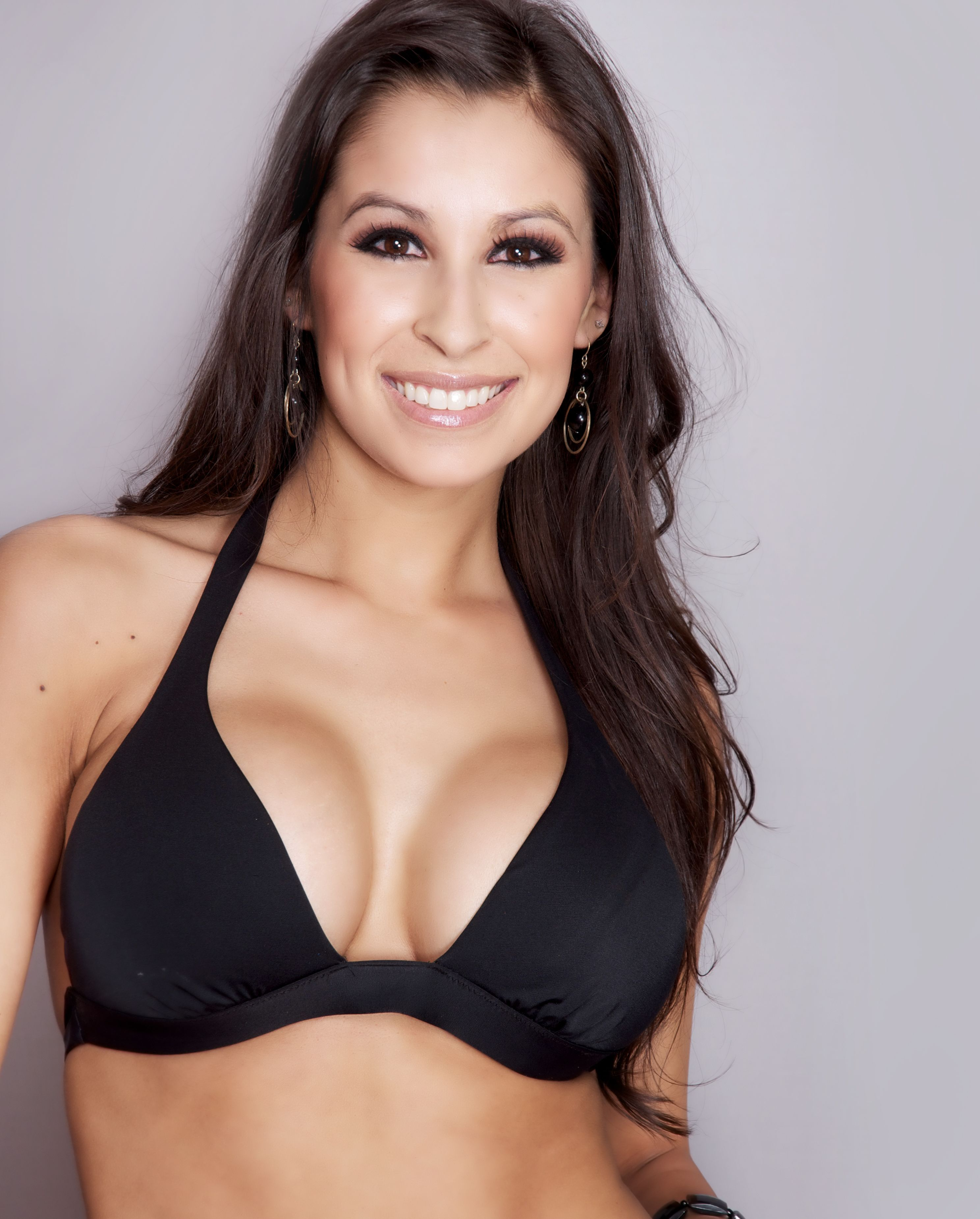 Smiling brunette in black bikini top with large, voluptuous breasts