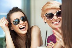Two women, wearing sunglasses and smiling, their teeth obviously not suffering from any form of tooth discoloration