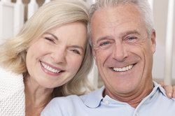 An older couple smiles together after their dental implant procedure