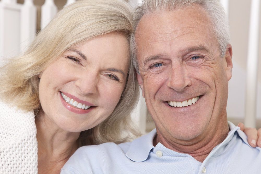 An older couple with dental implants smiles together