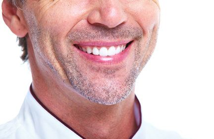 Middle-aged smiling man with very straight, white teeth