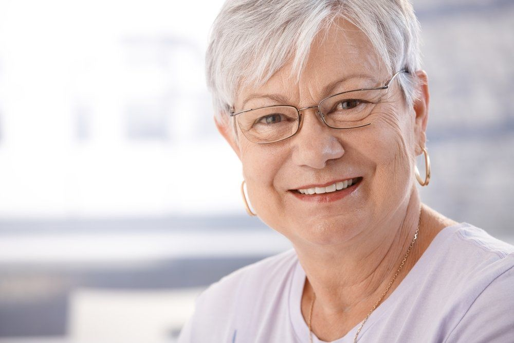 A woman smiling after recovering from a retinal artery occlusion