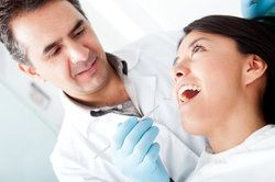 A dentist examining a woman's mouth